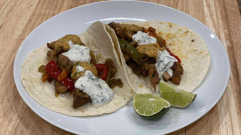 Two chicken fajitas on a plate with sliced lime