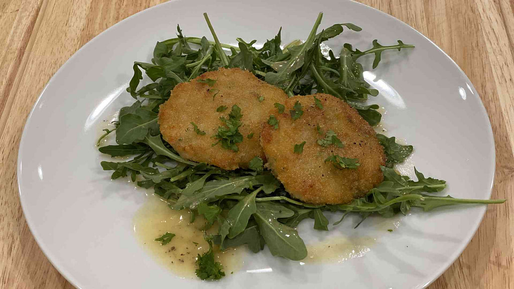 Two shrimp cakes on a plate with Beurre Blanc Sauce and arugula greens