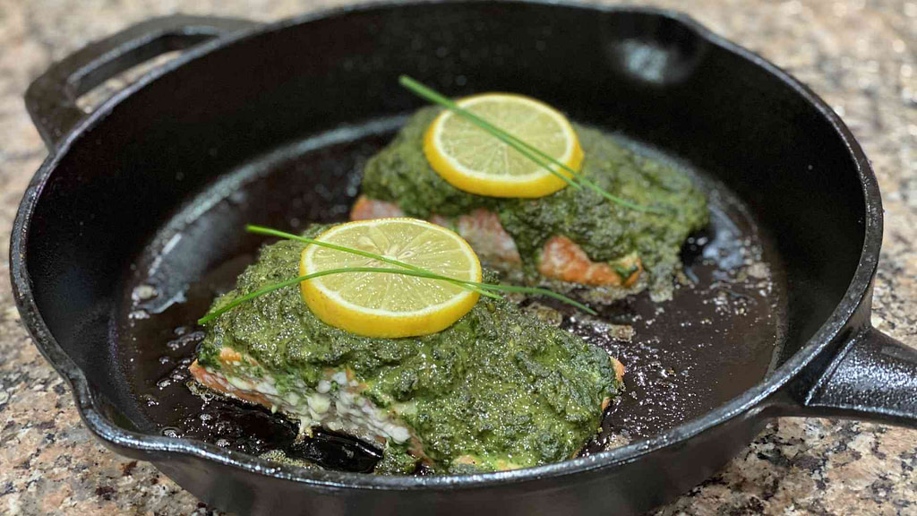 Baked salmon pesto on a cast iron pan with lemon slices and spring onions on top