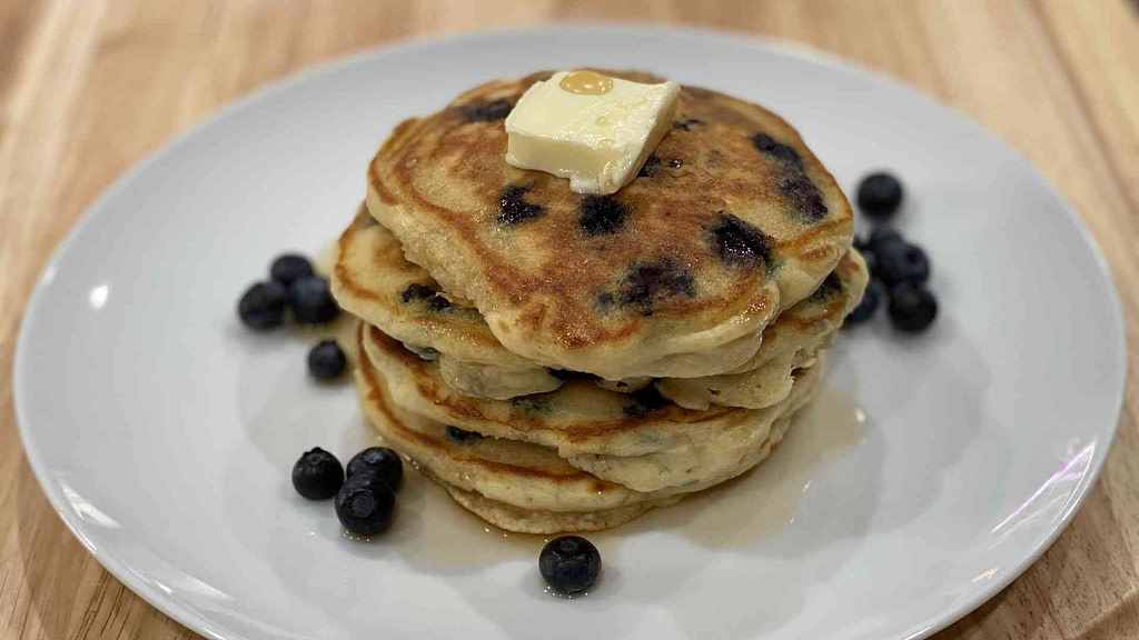 A stack of blueberry pancakes on a plate with butter and raw blueberries surrounding