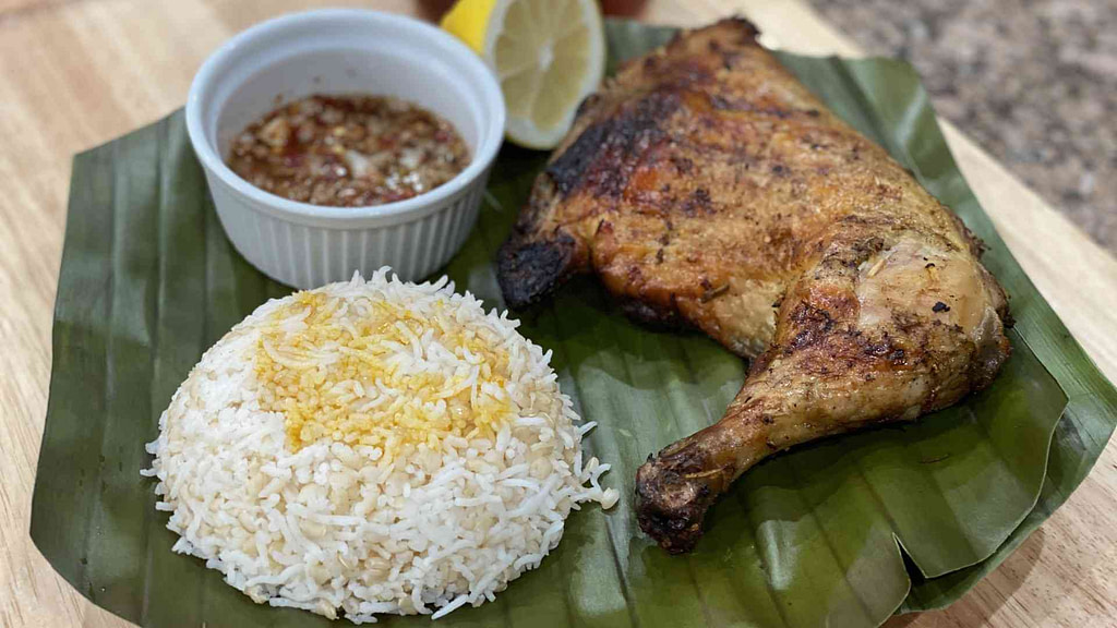 Filipino chicken inasal with rice on a banana leaf with sauce