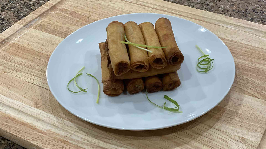 A stack of filipino lumpia shanghai on a plate with spring onions