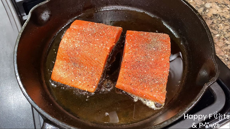 Two sockeye salmon fillets cooking in a cast iron pan with olive oil