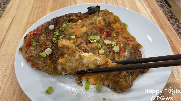 Two filipino style grilled eggplant omelets on a plate with onions and chopsticks