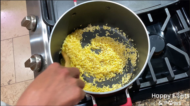 woman's hand stirring rice in pot on stove for Spanish rice recipe
