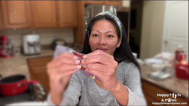 filipino woman in kitchen crushing dried red peppers in ziplock bag