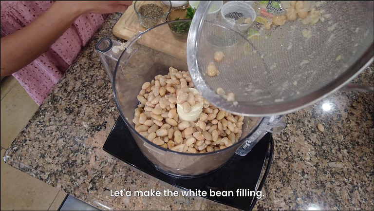 white beans being placed in food processor for white bean ravioli recipe