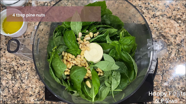 Fresh basil and pine nuts in a food processor for basil pesto