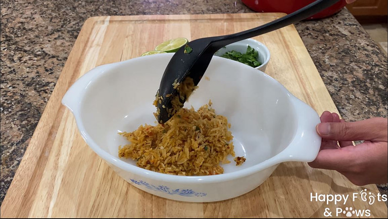 a scoop of spanish rice being added to a glass bowl