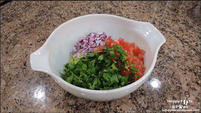 onions, cilantro, tomato in a bowl for guacomole recipe