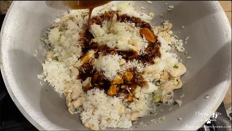 adding stir fry sauce to rice for thai chicken fried rice recipe