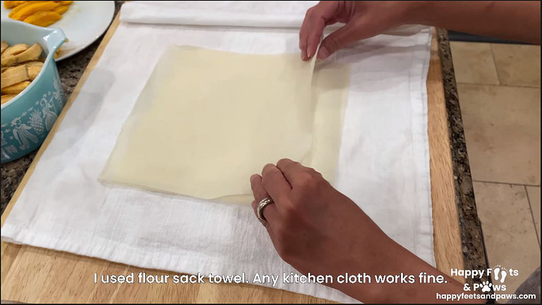 egg roll wrappers on damp cloth to keep them from drying out