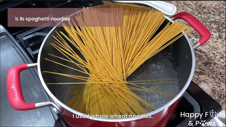spaghetti noodles being cooked in a pot of boiling water