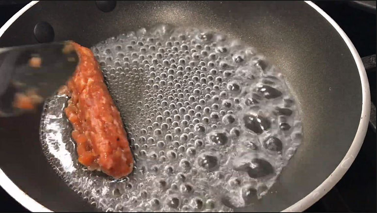 boiling water in a pan with one longanisa being placed inside