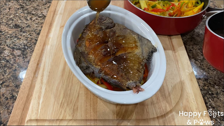 Adding sweet and sour sauce on fish in bowl