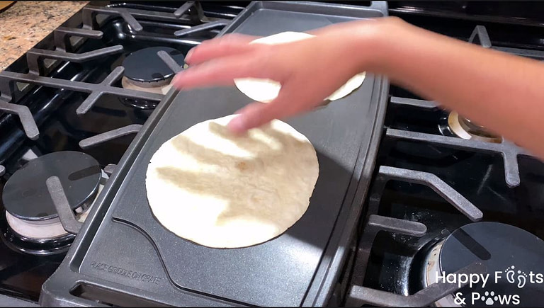 two tortillas on a skillet being warmed up