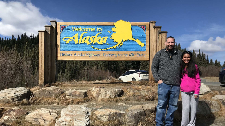 couple standing next to the welcome to alaska sign on the border between the Yukon and Alaska