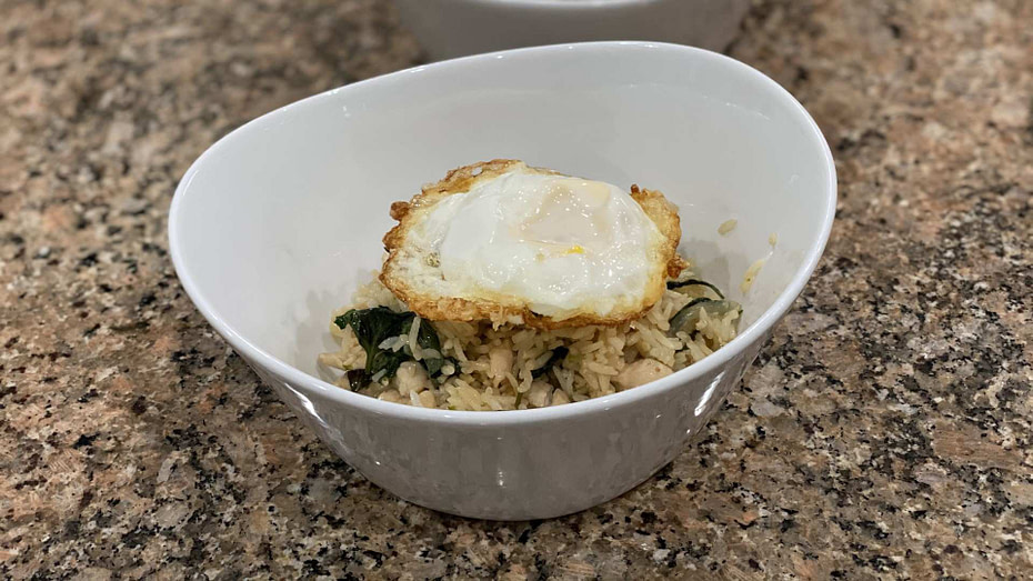 thai chicken fried rice with basil in a bowl. Fried egg on top